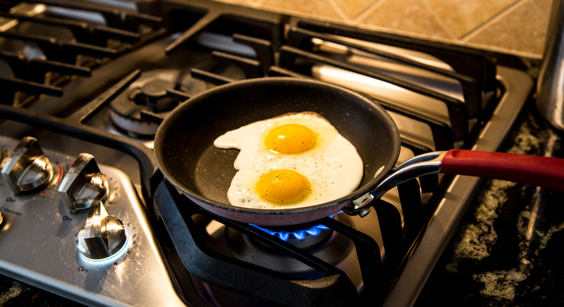 eggs frying in non-stick pan on gas stove