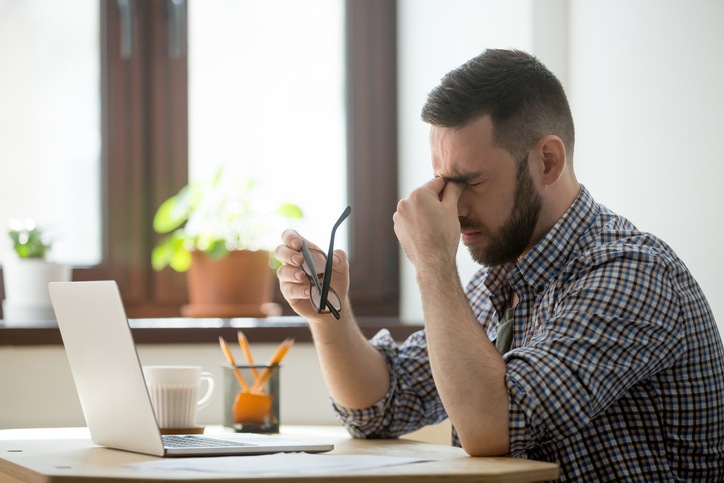 man with headache in workplace