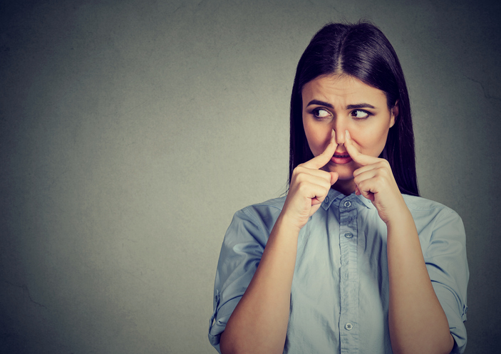 woman plugging nose - stale house smell