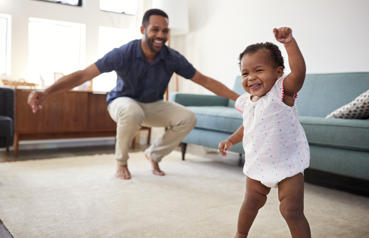 baby daughter dancing with father in living room