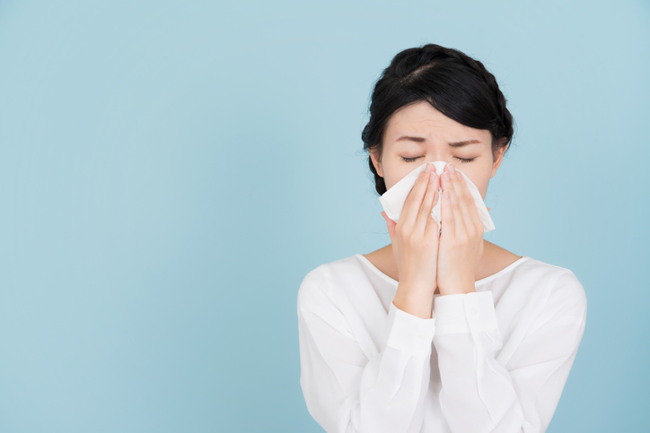 woman with allergies sneezing in tissue
